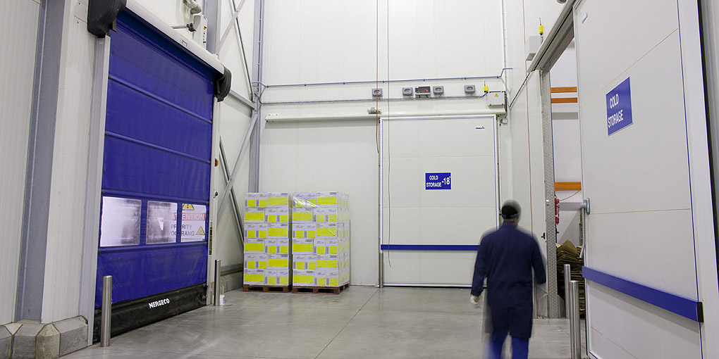 Flexible doors for food processing enclosing a cold storage air lock